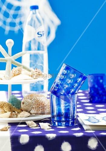 tisch mit blauer tischdecke blauen trinkgl sern muscheln auf etagere bild kaufen living4media. Black Bedroom Furniture Sets. Home Design Ideas