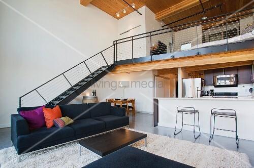 offenes wohnzimmer mit theke zur k che und treppenaufgang zur galerie bild kaufen living4media. Black Bedroom Furniture Sets. Home Design Ideas