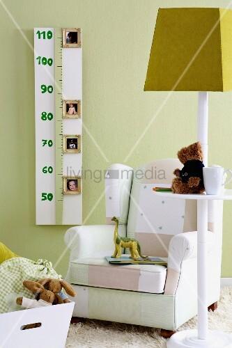 kinderzimmer feeling spielsachen auf stehleuchte mit ablage vor polstersessel an gr ner wand. Black Bedroom Furniture Sets. Home Design Ideas