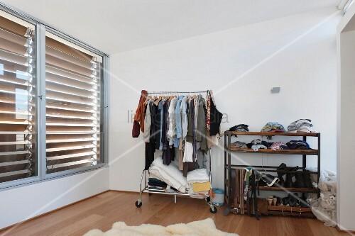 gef llter kleiderst nder und regal im schlafzimmer mit gro en jalousienfenstern bild kaufen. Black Bedroom Furniture Sets. Home Design Ideas