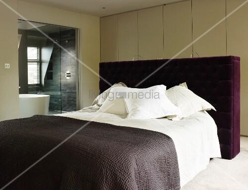 Doppelbett mit gepolstertem kopfteil und violettem bezug vor wandschrank in modernem - Wandschrank schlafzimmer ...