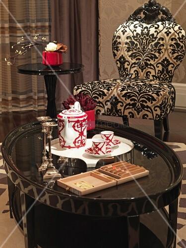 kleine beistelltische mit weissrotem teeservice und gemusterter polsterstuhl im antikstil bild. Black Bedroom Furniture Sets. Home Design Ideas