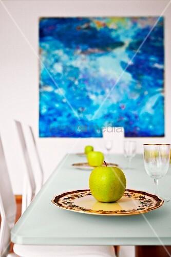 gr ne pfel auf dekorativen porzellantellern vor einem. Black Bedroom Furniture Sets. Home Design Ideas