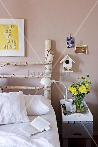 weiss bezogenes bett mit selbstgebautem kopfteil aus birkenholzst mmen und nistk stchen an der. Black Bedroom Furniture Sets. Home Design Ideas