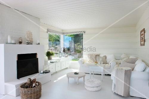 offener kamin gegen ber polstergarnitur und kleinen beistelltischen in offenem wohnzimmer mit. Black Bedroom Furniture Sets. Home Design Ideas