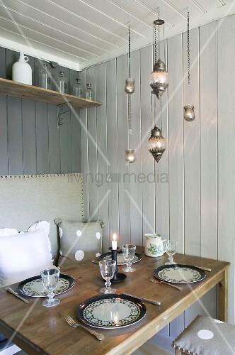 raumecke mit gedecktem esstisch in skandinavischem holzhaus mit sitzbank und r ckenpolster an. Black Bedroom Furniture Sets. Home Design Ideas