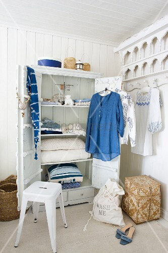 offener kleiderschrank mit an der t r h ngenden kleidungsst cken in blau und weiss rundherum. Black Bedroom Furniture Sets. Home Design Ideas