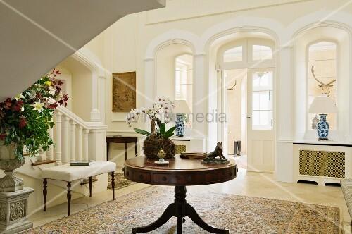 runder holztisch neben treppenaufgang und rundbogen t r im. Black Bedroom Furniture Sets. Home Design Ideas