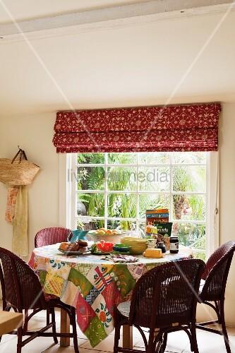 runder esstisch mit patchwork tischdecke und rattanst hlen. Black Bedroom Furniture Sets. Home Design Ideas