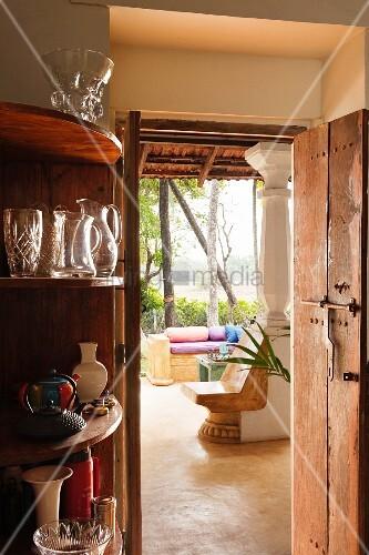 eckregal mit gl sern neben offener t r und blick durch wohnraum eines indischen wohnhauses in. Black Bedroom Furniture Sets. Home Design Ideas