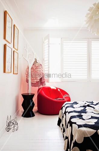 weisse schlafzimmerecke mit rotem polstersessel neben stilisiertem baum als kleiderst nder vor. Black Bedroom Furniture Sets. Home Design Ideas