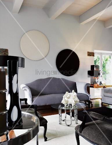 Graues, geschwungenes Sofa vor Wand mit runden Bildern und ...