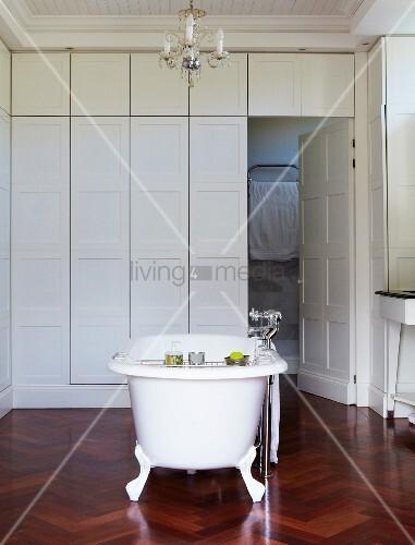freistehende vintage badewanne auf hochwertigem fischgr tboden aus dunklem holz in weissem bad. Black Bedroom Furniture Sets. Home Design Ideas
