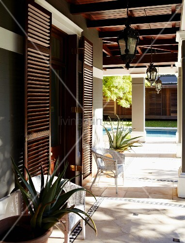elegantes wohnhaus mit t rl den aus holz und umlaufender berdachung auf s ulen vor pool im. Black Bedroom Furniture Sets. Home Design Ideas