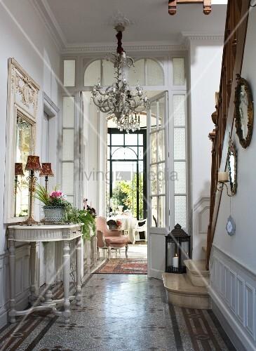 elegante diele mit barockem wandtisch kronleuchter und treppenaufgang mit steinstufen und. Black Bedroom Furniture Sets. Home Design Ideas