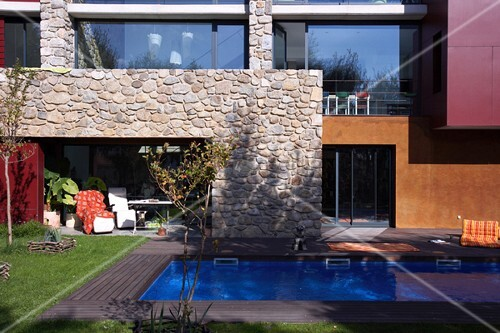 swimmingpool im garten vor modernem geb ude mit natursteinwand bild kaufen living4media. Black Bedroom Furniture Sets. Home Design Ideas