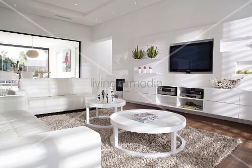 weisses wohnzimmer mit weisser ledersofagarnitur und kreisf rmige couchtische auf flokatiartigem. Black Bedroom Furniture Sets. Home Design Ideas