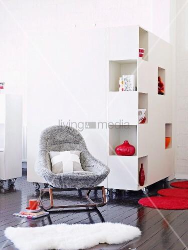 weisser rollenschrank auf gl nzendem dunklen parkett davor ein gepolsteter schaukelstuhl. Black Bedroom Furniture Sets. Home Design Ideas