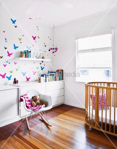 klassiker schaukelstuhl neben kindergitterbett und weisses sideboard an wand mit. Black Bedroom Furniture Sets. Home Design Ideas