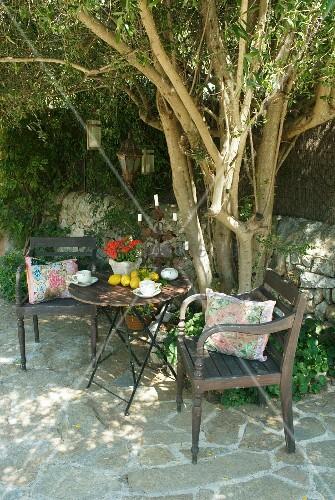 vintage gartenst hle mit tisch vor baum auf terrassenboden aus naturstein bild kaufen. Black Bedroom Furniture Sets. Home Design Ideas