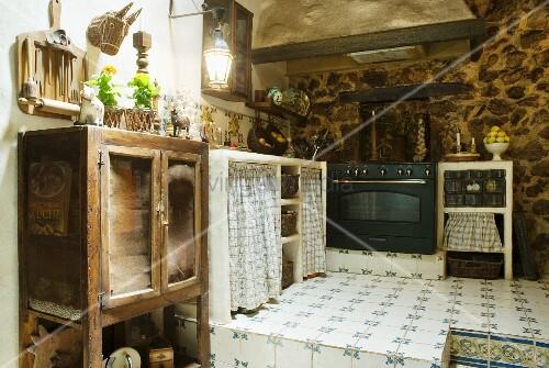 alte k cheneinrichtung mit modernem herd auf gefliestem podest im rustiko bild kaufen. Black Bedroom Furniture Sets. Home Design Ideas