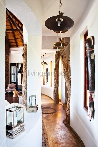 geschwungener flur mit baumst mmen als deckenst tzen und ethnokunst an den w nden bild kaufen. Black Bedroom Furniture Sets. Home Design Ideas