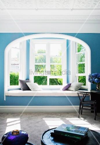 blaues jugendstil wohnzimmer mit sitzbank in fensternische und gartenblick bild kaufen. Black Bedroom Furniture Sets. Home Design Ideas