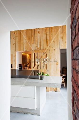 Küchentheke aus Beton mit eingebautem Unterschrank und Schubladen vor Holzwand u2013 Bild kaufen