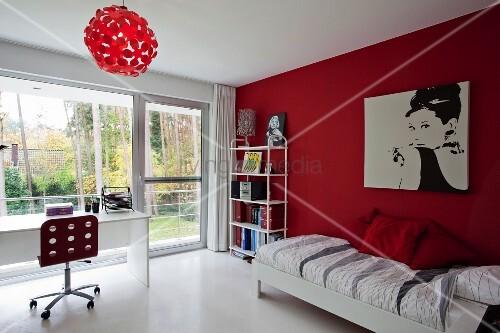 jugendzimmer mit bett vor roter wand und bild von audrey hepburn gegen ber der schreibtisch mit. Black Bedroom Furniture Sets. Home Design Ideas