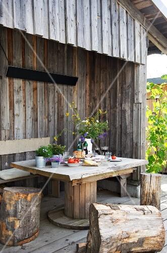 tisch mit bank und baumstamm hockern auf der terrasse einer holzh tte bild kaufen living4media. Black Bedroom Furniture Sets. Home Design Ideas