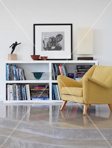 50er Jahre Sessel vor halbhohem Regal auf Podest mit Stufen aus ...