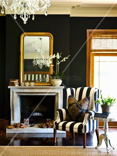 schwarz weiss gestreifter sessel neben offenem kamin und spiegel mit goldrahmen an schwarz. Black Bedroom Furniture Sets. Home Design Ideas