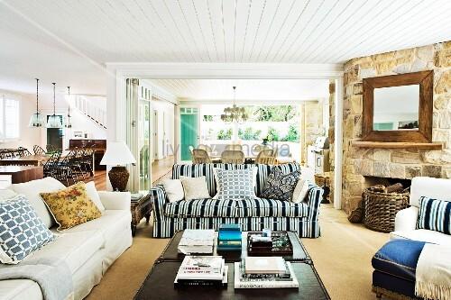 weitl ufiger wohnraum im hampton stil mit rustikaler steinwand und offenem kamin im wohnbereich. Black Bedroom Furniture Sets. Home Design Ideas