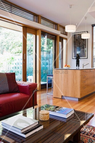 blick ber sofatisch mit glasplatte und rotes ledersofa auf k chentheke vor fensterfront zum. Black Bedroom Furniture Sets. Home Design Ideas