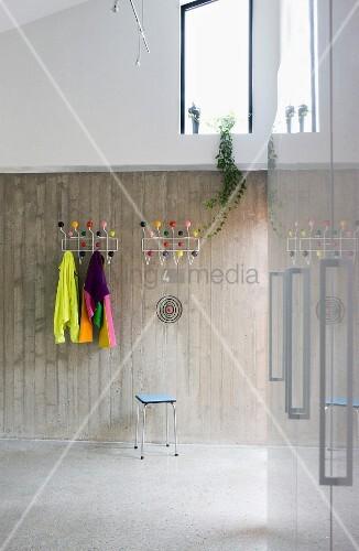 garderobe mit bunten kugeln an sichtbetonwand in modernem vorraum bild kaufen living4media. Black Bedroom Furniture Sets. Home Design Ideas