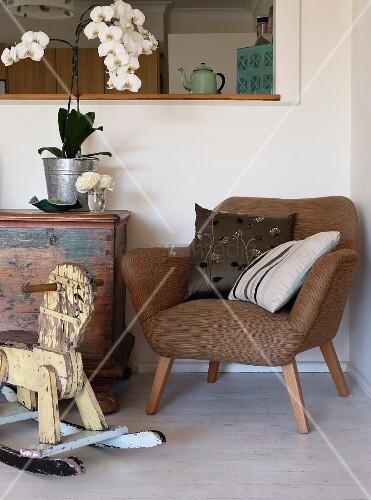 vintage schaukelpferd vor sessel im 50er jahre stil in zimmerecke unter durchreiche bild. Black Bedroom Furniture Sets. Home Design Ideas