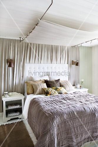 graue tagesdecke auf doppelbett mit gepolstertem kopfteil. Black Bedroom Furniture Sets. Home Design Ideas