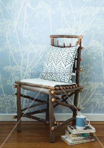 kissen auf selbstgebautem stuhl aus naturbelassenen sten neben b cherstapel auf boden vor wand. Black Bedroom Furniture Sets. Home Design Ideas