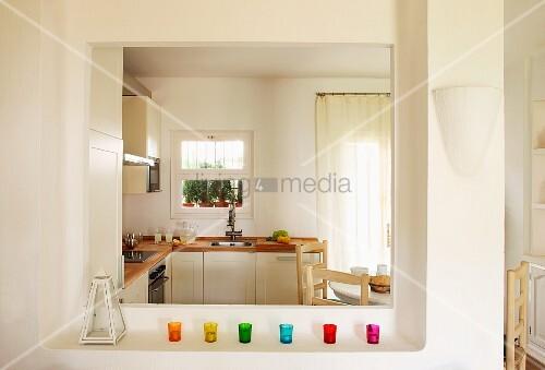 bunte windlichtgl ser auf ablage vor durchreiche und blick in eine helle moderne k che bild. Black Bedroom Furniture Sets. Home Design Ideas