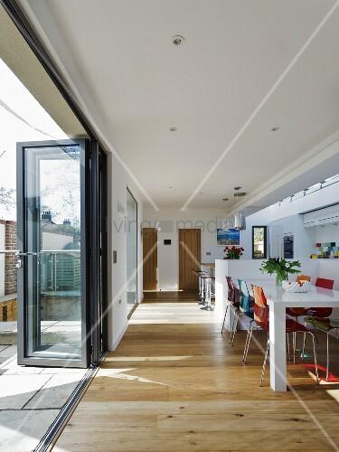 essplatz mit farbigen st hlen auf holzboden in offenem. Black Bedroom Furniture Sets. Home Design Ideas