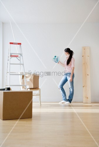 Frau h lt farbmuster an die wand bild kaufen living4media - Farbmuster wand ...