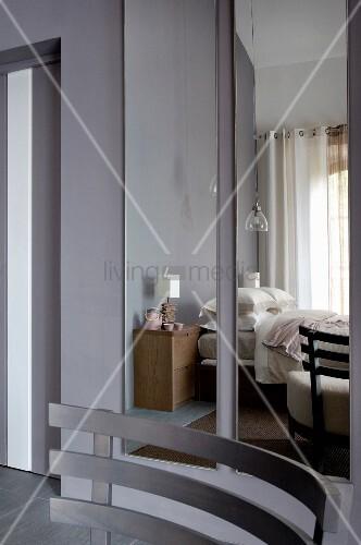 holz r ckenlehne eines sessels vor spiegel mit reflektiertem schlafzimmer an grauer wand bild. Black Bedroom Furniture Sets. Home Design Ideas
