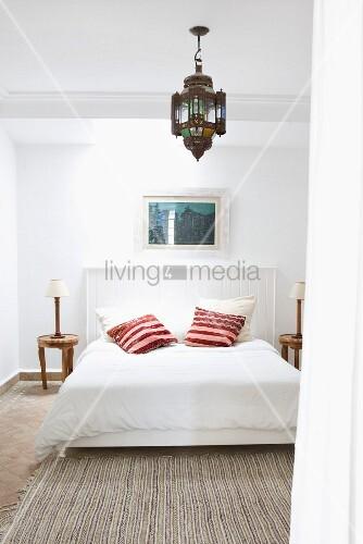 einfaches bett mit holzverschaltem kopfteil und bunten kissen unter orientalischer h ngelampe. Black Bedroom Furniture Sets. Home Design Ideas