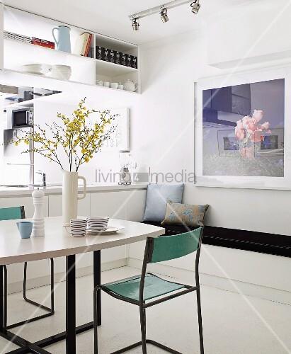 minimalistischer essplatz vor offener k che mit deckenregal ber der theke bild kaufen. Black Bedroom Furniture Sets. Home Design Ideas