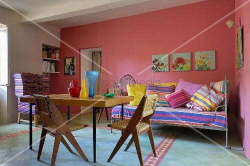 esstisch und st hle mit geflecht im 50er jahre stil vor tagesbett mit kissen im streifenlook an. Black Bedroom Furniture Sets. Home Design Ideas