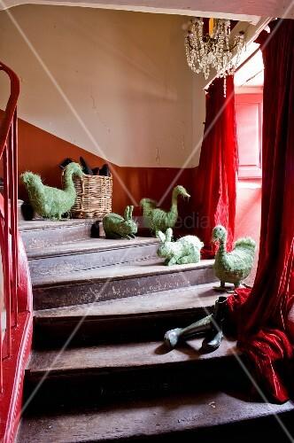 alte holztreppe mit tierfiguren aus stroh auf stufen und roter vorhang am fenster bild kaufen. Black Bedroom Furniture Sets. Home Design Ideas