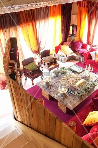 blick von treppe in loungebereich mit raumteiler aus holz und grosser selbstgebauter tisch mit. Black Bedroom Furniture Sets. Home Design Ideas