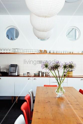 drei bullaugen ber k chenzeile mit einfachem gl serbord und h ngelampen mit papierschirm ber. Black Bedroom Furniture Sets. Home Design Ideas