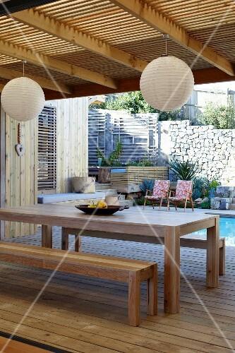 Holztisch mit b nken und kugelf rmige h ngelampen auf einer berdachte terrasse vor pool bild - Holztisch terrasse ...