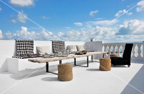Schwarzweiss karierte decken auf gemauerter bank und rustikaler holztisch mit basthockern auf - Holztisch terrasse ...